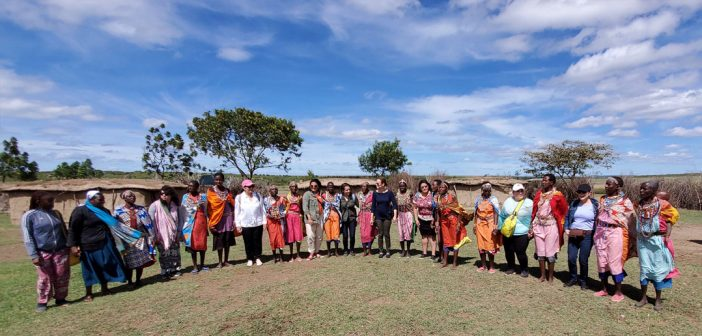 A panoramic shot of African women and Fordham students and staff standing side by side against a bright blue sky
