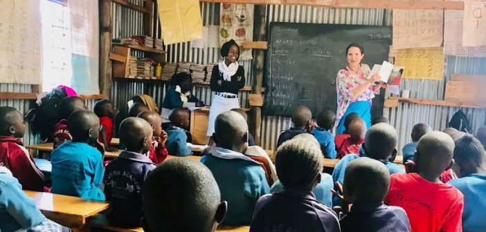 A woman stands in front of a chalkboard in front of a large classroom filled with children