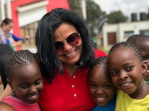 A Hispanic woman wearing a red shirt and sunglasses smiles and holds three young Kenyan children