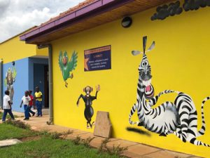 A bright yellow building wall with painted cartoon animals
