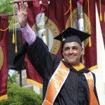 A graduate waving.