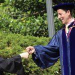 A graduate fist bumping a faculty member.