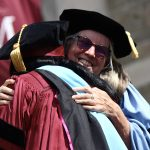 A graduate hugging former dean Virginia Roach.